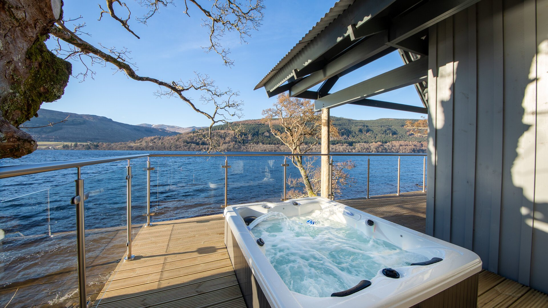 hot tub on decking overlooking loch tay from boathouse on stilits